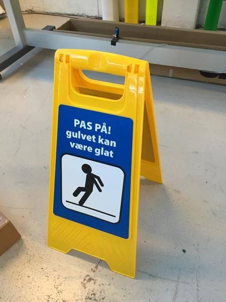 Pas på gulvet kan være glat. Gult gulvskilt